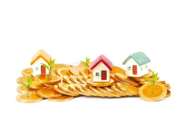 Minihaus auf münzenstapel mit wecker und wachsen anlage