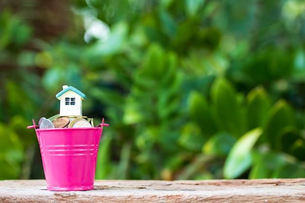 Minihaus auf stapel münzen. konzept der als finanzinvestition gehaltenen immobilien.
