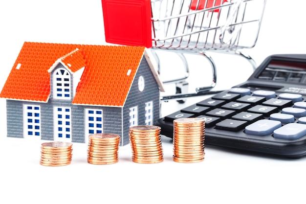 Minihaus auf stapel münzen. konzept der investment property. kaufkonzept