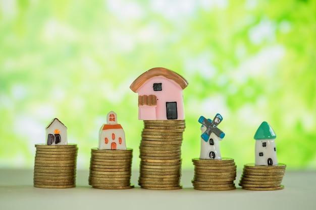 Minihaus auf stapel münzen mit grüner unschärfe.