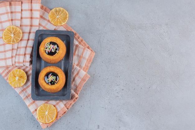 Minikuchen mit gelee und fruchtscheiben auf steintisch.