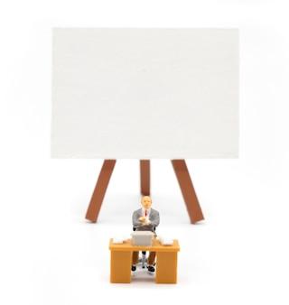 Minilehrer vor einer tafel auf weißem hintergrund. zurück zum schulkonzept.