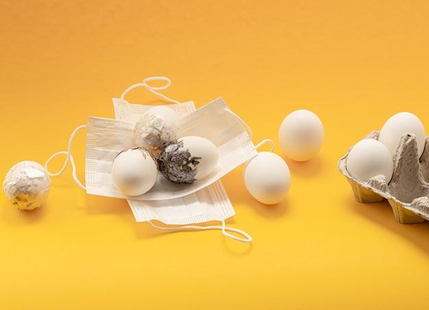 Minimal dekorierte ostereier sind gegen das coronavirus maskiert. sicheres osterfestkonzept.