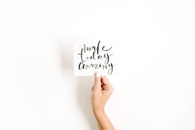 Minimale blasse zusammensetzung mit handhandkarte des mädchens mit zitat make today amazing, geschrieben im kalligraphischen stil auf papier auf weißer oberfläche