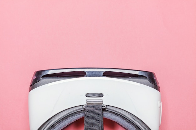 Minimale einfache ebenenlage mit glassturzhelmkopfhörer der virtuellen realität vr auf rosa modischem modernem pastellhintergrund