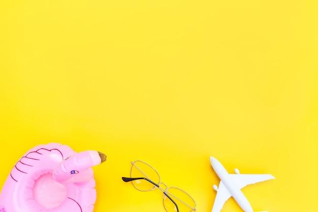 Minimale einfache flache lage mit flacher sonnenbrille und aufblasbarem flamingo, isoliert auf gelb