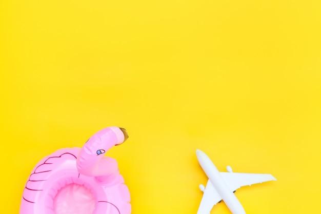 Minimale einfache flache lage mit flugzeug und aufblasbarem flamingo, isoliert auf gelb