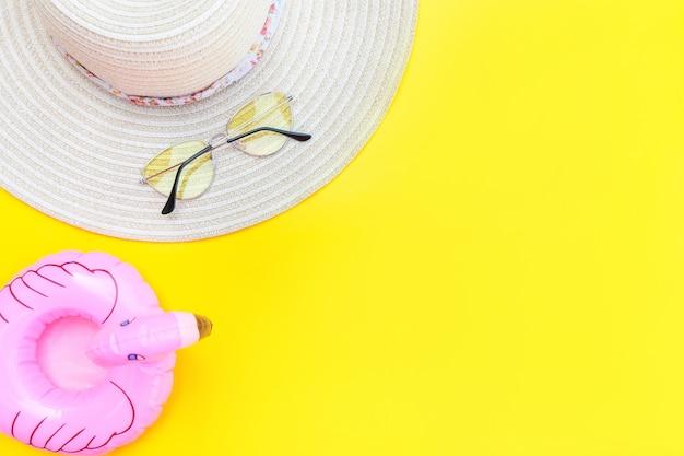 Minimale einfache flache lage mit sonnenbrillenhut und aufblasbarem flamingo, isoliert auf gelb