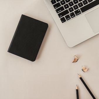 Minimale flache lage, lifestyle-komposition von oben mit laptop, bleistiften, notizbuch auf neutralem pastellbeige.
