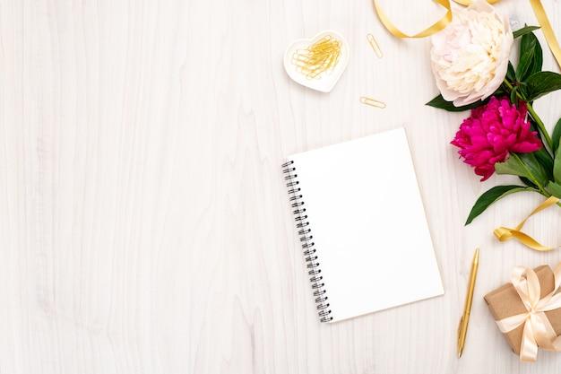 Minimale flächige komposition mit notizblock aus papier, pfingstrosenblüten, geschenkbox und femininen accessoires. draufsichtfrauen-innenministeriumschreibtisch. modeblog-fahnenschablone mit kopienraum