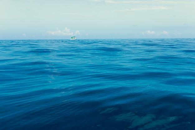 Minimale fotografie des fischereibootes, das über blaue seewelle schwimmt