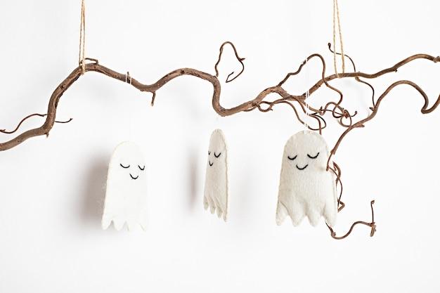 Minimale halloween-dekoration, die auf ast lokalisiert hängt
