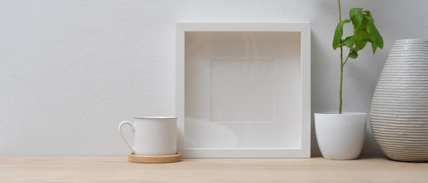 Minimale inneneinrichtung mit modellrahmen, vase, blumentopf und kopierraum auf holztisch
