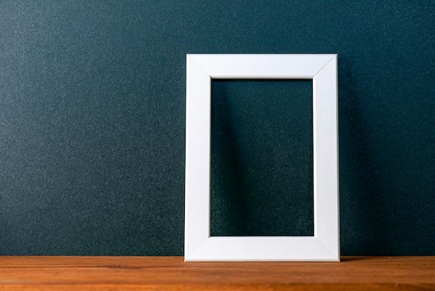 Minimale innenkomposition mit schwarzer wand und weißem leerem bilderrahmen auf dem holztisch, dekormodell, platz für text