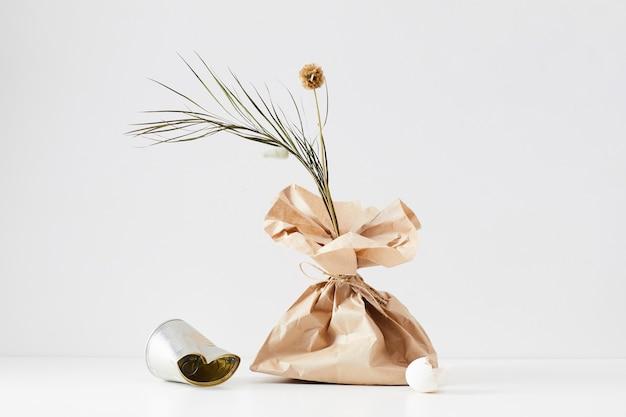 Minimale komposition aus müllartikeln mit floralem akzent