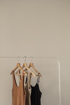 Minimale mode für damen in pastellfarben. stilvolle weibliche t-shirts, oberteile auf kleiderständer auf weiß