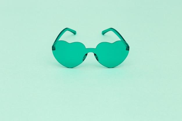 Minimale modefotografie mit herzförmiger brille hellgrüne moderne sonnenbrille. sommerkonzept.