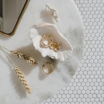 Minimale modekomposition mit goldenen ohrringen in muschel auf marmortisch mit spiegel und weizenstielen.