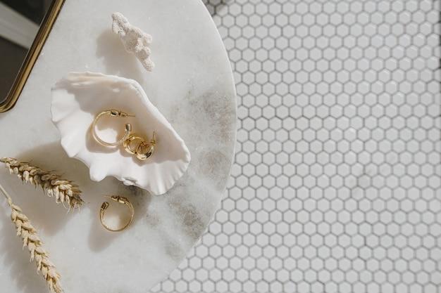 Minimale modekomposition mit goldenen ohrringen in muschel auf marmortisch mit spiegel und weizenstielen
