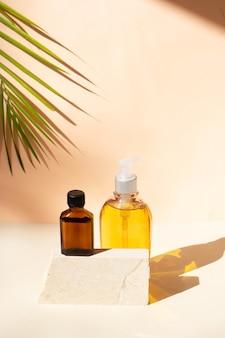 Minimale moderne kosmetikprodukte zeigen zwei flaschen essenzöl auf beigem hintergrund mit schattenüberlagerung