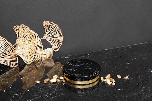 Minimale moderne produktpräsentation auf schwarzen und goldenen abstrakten blumen auf dem hintergrund mit podium, luxuriöser art-deco-stil der 20er jahre