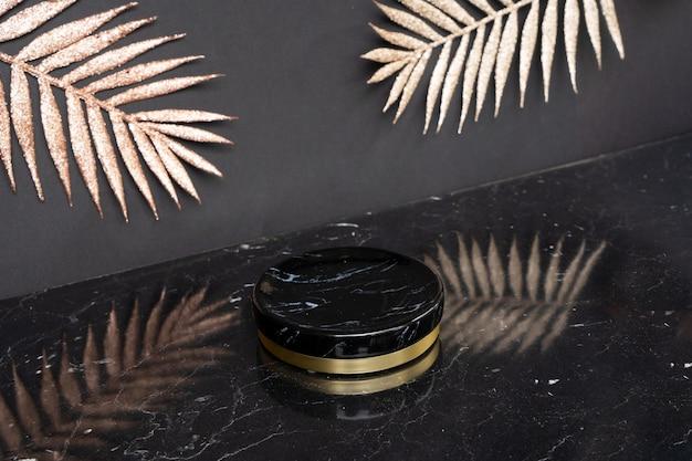 Minimale moderne produktpräsentation auf schwarzen und goldenen palmblättern auf dem hintergrund mit podium, luxuriöser art-deco-stil der 20er jahre