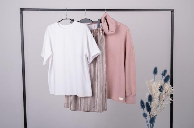 Minimale pastellkleidung für damen. stilvolle weibliche t-shirts, hoodie, hosen auf kleiderbügel