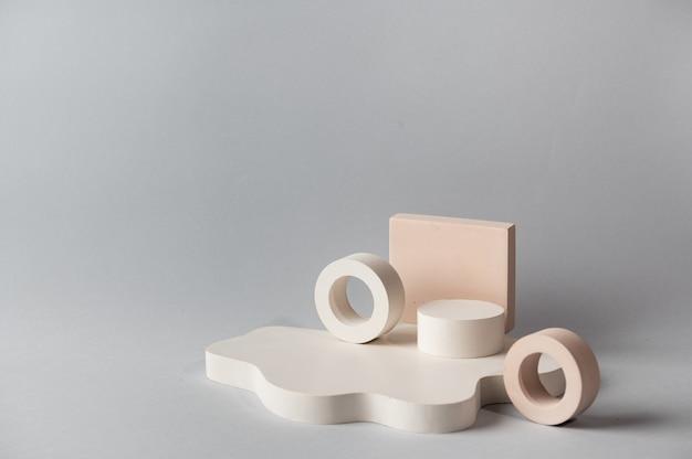 Minimaler abstrakter kosmetischer hintergrund für die produktpräsentation. kosmetisches flaschenpodest auf grauem farbhintergrund. pastellfarben gestaltete komposition mit geometrischen formen. minimales konzept. produktmodell