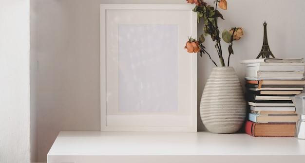 Minimaler arbeitsbereich mit leerem fotorahmen und trockenem rosenvase