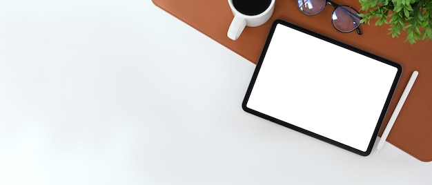 Minimaler arbeitsplatz mit digitalem tablet, stylus-stift, kaffeetasse und zimmerpflanze auf weißem schreibtisch.