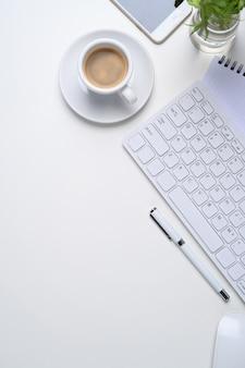 Minimaler arbeitsplatz mit kabelloser tastatur, kaffeetasse, mobiltelefon, pflanzen- und kopierraum auf weißem hintergrund.