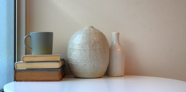 Minimaler arbeitsplatz mit keramischen vasen auf weißer tabelle mit büchern und kaffeetasse