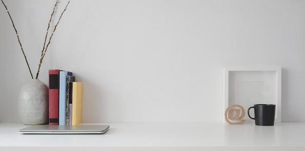 Minimaler arbeitsplatz mit kopienraum und büroartikel auf weißem holztisch und weißer wand