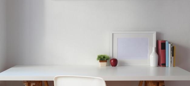 Minimaler arbeitsplatz mit kopienraum und leerem rahmen mit büchern auf weißer tabelle und weißer wand