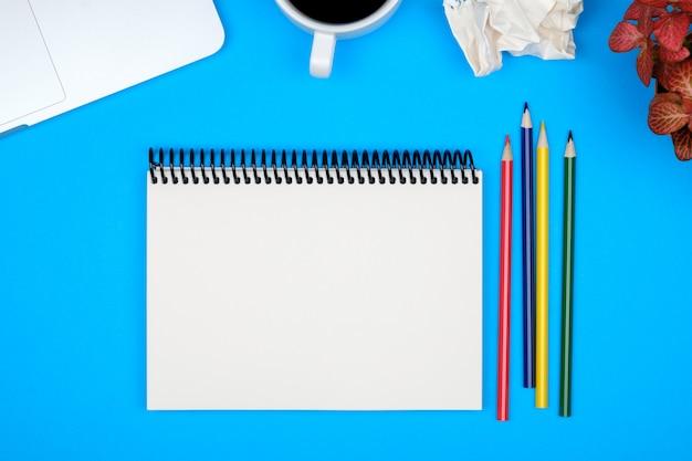 Minimaler arbeitsplatz mit laptop und leerem notizblock
