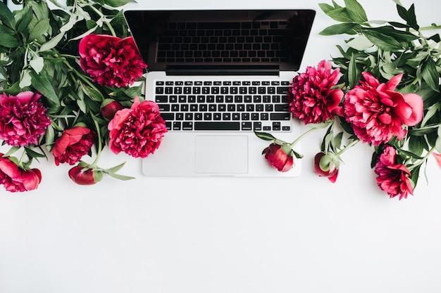 Minimaler arbeitsplatz mit laptop und rosa pfingstrosenblumen auf weißem hintergrund. flache lage, ansicht von oben