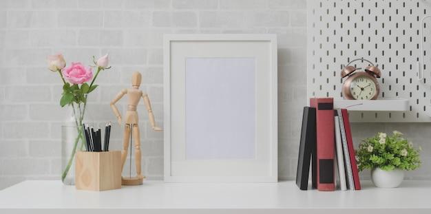 Minimaler arbeitsplatz mit modell herauf rahmen, bücher und dekorationen auf weißer tabelle und grauer backsteinmauer