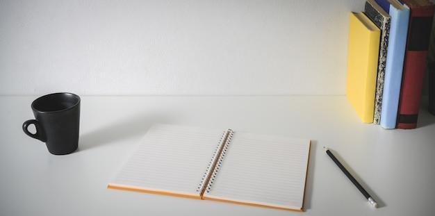 Minimaler arbeitsplatz mit offenem leerem notizbuch, büroartikel, kaffeetasse und kopienraum
