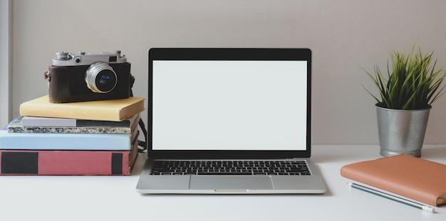 Minimaler arbeitsplatz mit offener laptop-computer des leeren bildschirms auf weißem schreibtisch