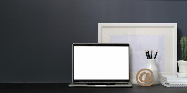 Minimaler arbeitsplatz mit offener laptop-computer des leeren bildschirms und modell herauf rahmen