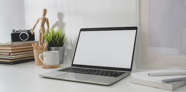 Minimaler arbeitsplatz mit offener laptop-computer des leeren bildschirms und weinlesekamera