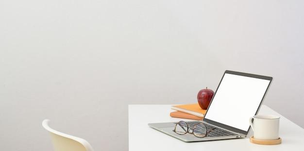 Minimaler arbeitsplatz mit offener laptop-computer und büroartikel auf weißem schreibtisch