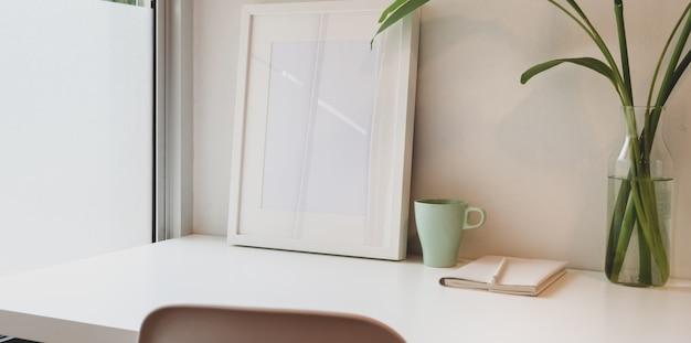 Minimaler arbeitsplatz mit verspottetem rahmen- und kopienraum