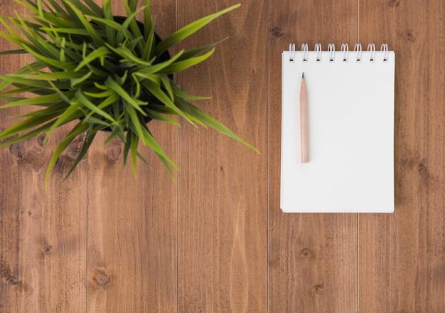 Minimaler arbeitsplatz, notizbuch und brauner bleistift auf hölzernem tabellenhintergrund