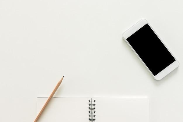 Minimaler arbeitsraum - kreativ flach legen foto von arbeitsbereich schreibtisch mit skizzenbuch und handy mit leeren bildschirm auf kopie raum weißen hintergrund. draufsicht, flache laienfotografie.
