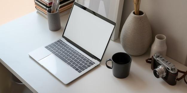 Minimaler büroraum nahe bei den fenstern mit offenem laptop des leeren bildschirms