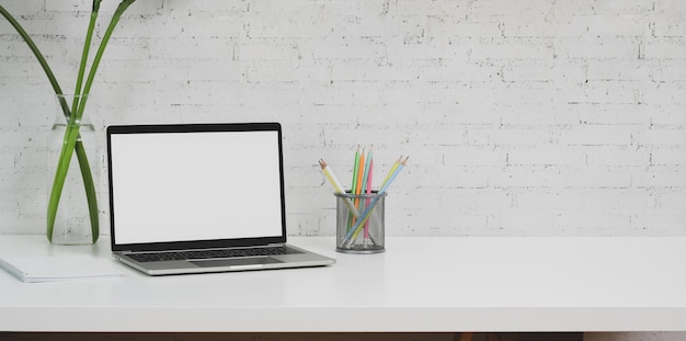 Minimaler designerarbeitsplatz mit laptop-computer und bürozubehör