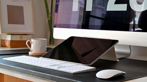 Minimaler desktop des loft-arbeitsbereichs mit modell-desktop-computer und tablet.