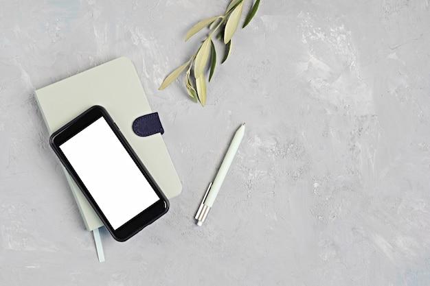 Minimaler desktop mit organischen farben, stationär und smartphone