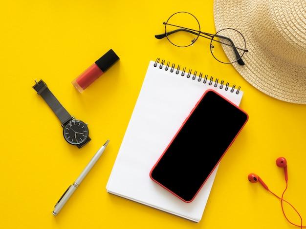 Minimaler flacher arbeitsbereich mit smartphone-modell mit leerem bildschirm, brille, strohhut und notizbuch. kopieren sie den speicherplatz für den site-screenshot oder die mobile app.